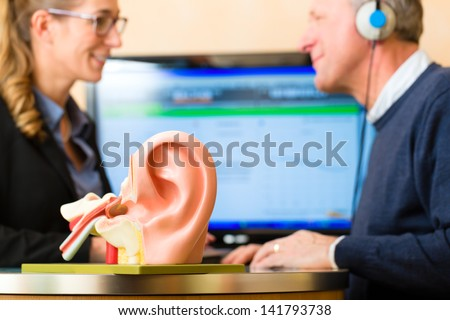 Older man or pensioner with a hearing problem make a hearing test and may need a hearing aid, in the foreground is a model of a human ear - stock photo
