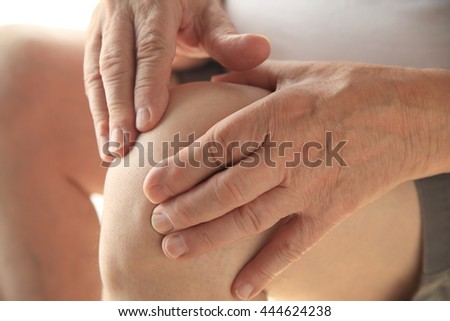 Older man puts both hands on an aching knee. - stock photo