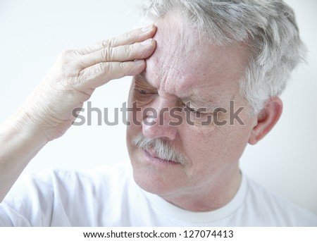 older man puts his fingers against his forehead while frowning in pain