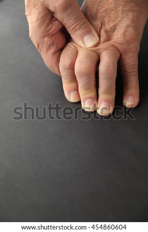 Older man rubs his painful knuckles. - stock photo