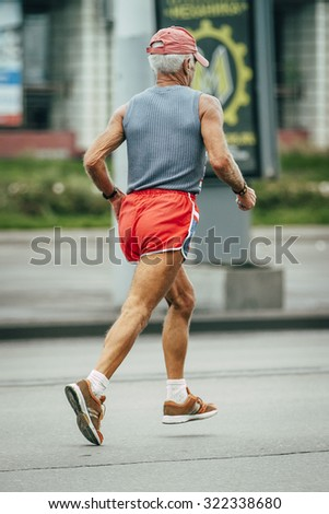 older man runs through the streets of the city, participating in marathon