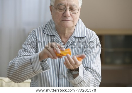 Older man shaking out pills into his hand - stock photo