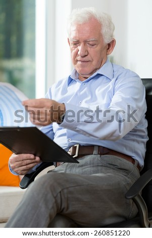 Older man sitting on chair and reading notes - stock photo