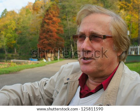 Older man taking a break in the park sitting in the shade on a bench - stock photo