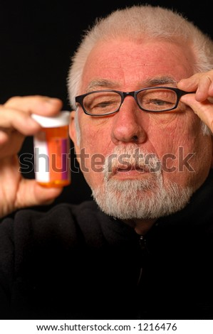 Older man tries to read pill bottle - stock photo