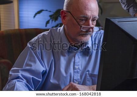 Older man using his computer at night, horizontal - stock photo