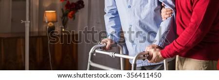 Older man walking with walker in caregiver's assistance - stock photo