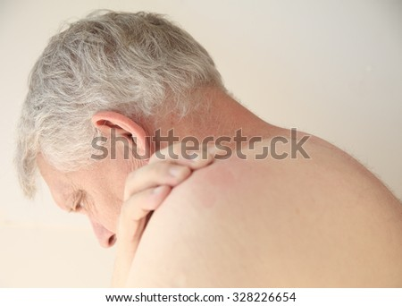 Older man with an itchy rash on his back - stock photo