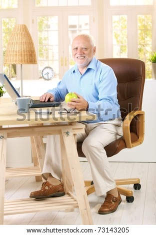 Older man working in his study at home, using computer, holding apple, looking at camera, smiling.?