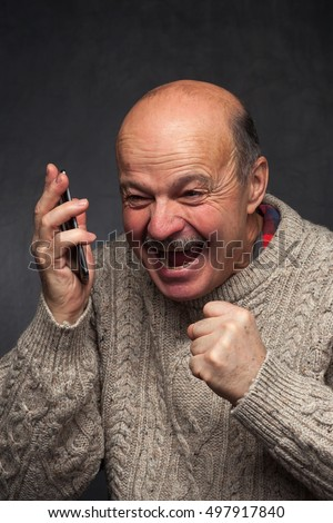 older man yells into the phone in anger. Screaming at interlocutor in conversation.