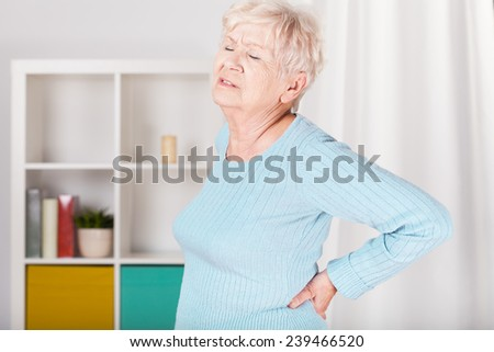 Older nice lady with terrible backache - stock photo