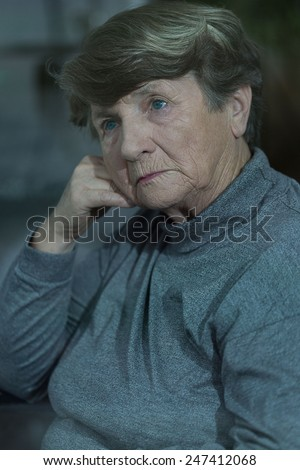 Older pensive woman contemplating her life - stock photo