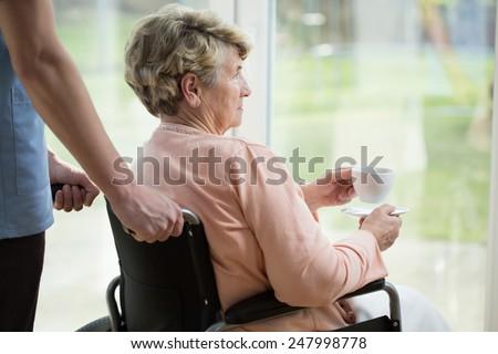 Older sad woman on wheelchair looking through the window - stock photo
