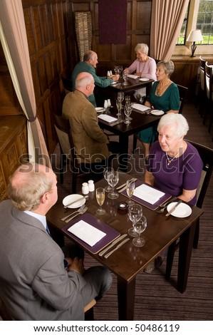 Older senior couples sitting in smart restaurant - stock photo