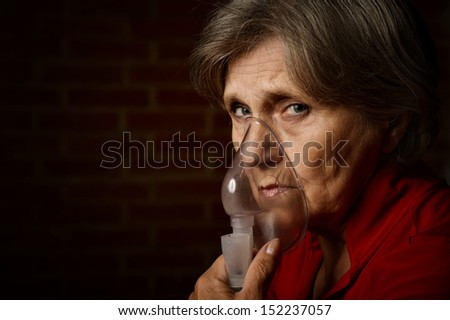 Older sick woman with inhaler in red on a background of a brick