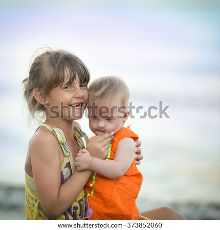 older sister holds a beautiful girl with Down syndrome - stock photo