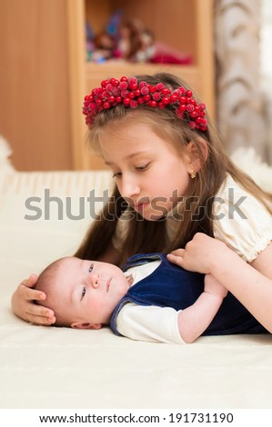Older sister hugging baby lying on the bed  - stock photo