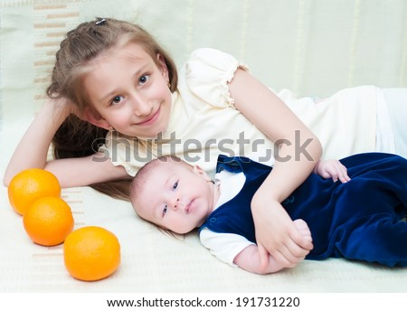 Older sister hugging baby lying on the bed with oranges - stock photo