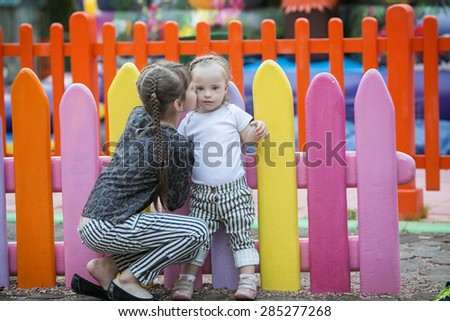older sister kissing a beautiful girl with Down syndrome - stock photo