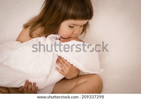 Older sister kissing his newborn sister. Beautiful little girl with a newborn baby in her arms