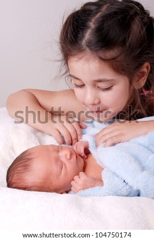 older sister looking at newborn baby brother - stock photo