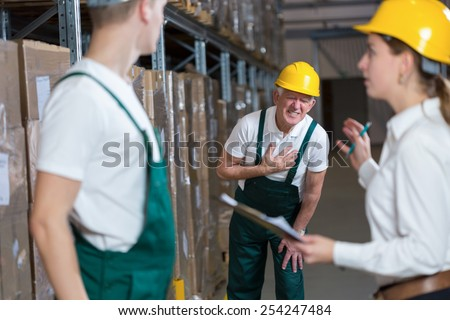 Older warehouseman having a painful infarction - stock photo