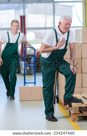 Older warehouseman having pain in his chest - stock photo