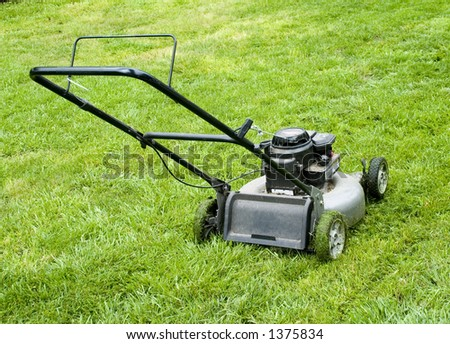 Older, well used lawn mower on very green lawn.