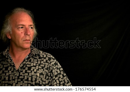 older white male with grey hair and blue eyes wearing patterned shirt, looking left into darkness. - stock photo