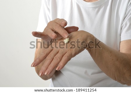 Older woman applying cream on hands closeup on white background