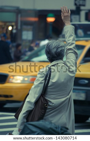 Older Woman Calling Taxi in New York City Street - stock photo