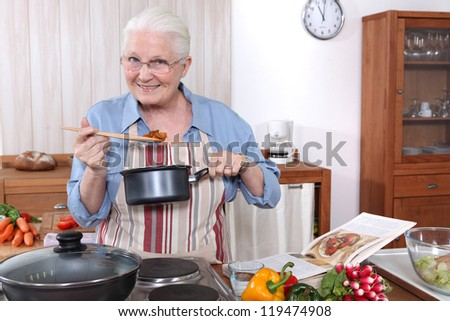 Older woman cooking a meal - stock photo