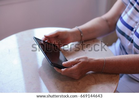 Older woman holding tablet on the table