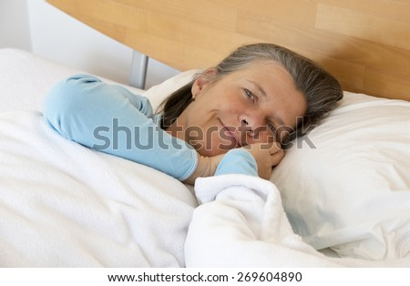 older woman in bed and smiling peacefully