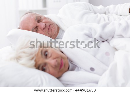 Older woman is already awaked and her husband is still sleeping
