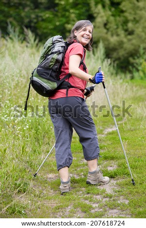 older woman is hiking in nature - stock photo
