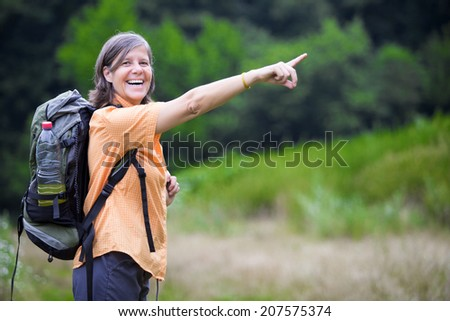 older woman is hiking in nature and pointing to something - stock photo
