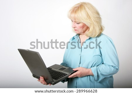 Older woman looking at her laptop computer with a serious or quizzical look on her face. - stock photo