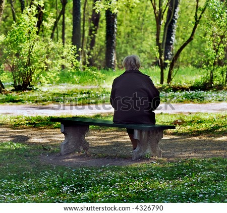 Older woman sit on bench in park