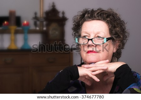 Older woman smiling in her living room. Smiling friendly senior woman sitting on a chair in her living room. Elderly woman. - stock photo