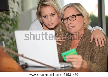 Older woman using a card online - stock photo