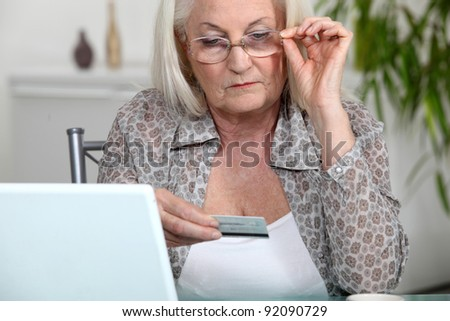 Older woman using her credit card online - stock photo