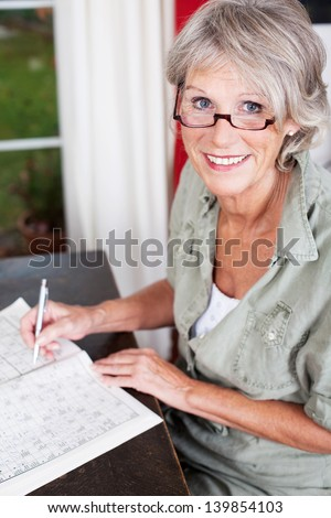 Older woman wearing glasses working on a crossword puzzle in a puzzle book sittiing at a small wooden table in her house