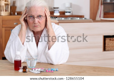 Older woman with medicine - stock photo