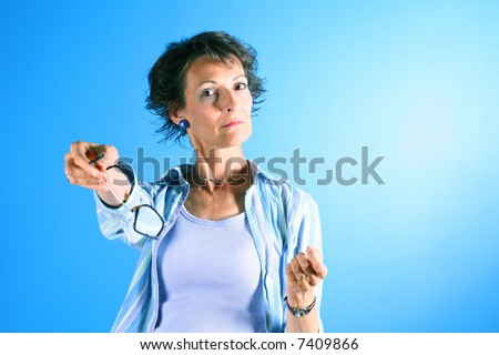 older woman with stern expression holding out glasses