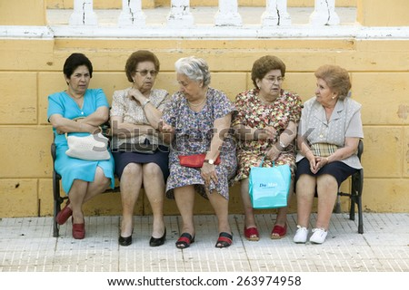 Older women sit on bench in village of Southern Spain off highway A49 west of Sevilla - stock photo