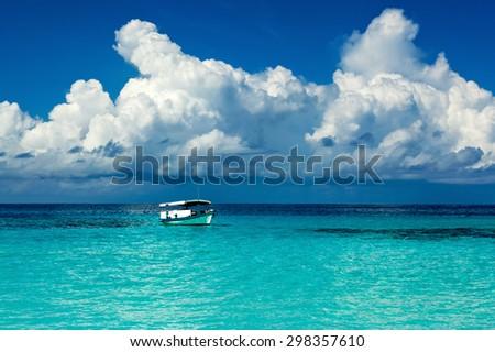 oldest boat of in the tropical lagoon turquoise Caribbean Sea in the Maldivian Hawaiian Bahamas - stock photo