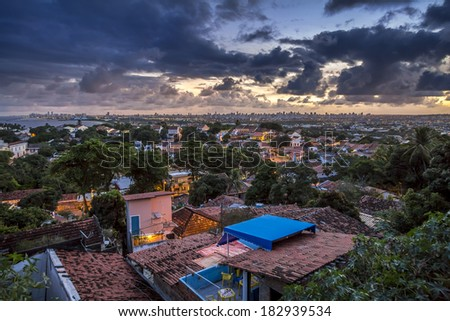 OLINDA, BRAZIL - MARCH 17: Aerial view of the historic buildings of Olinda in Pernambuco, Brazil and Recife's skyscrapers in the background at sunset on March 17, 2014. - stock photo