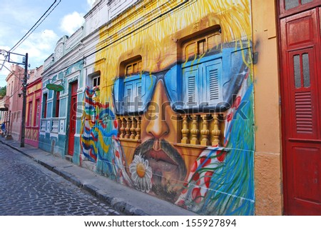 OLINDA, RECIFE, PERNAMBUCO, BRAZIL, JANUARY 8 2008. A wall full of illegal graffiti. A wall painting of a man's head with moustache and sunglasses.  - stock photo