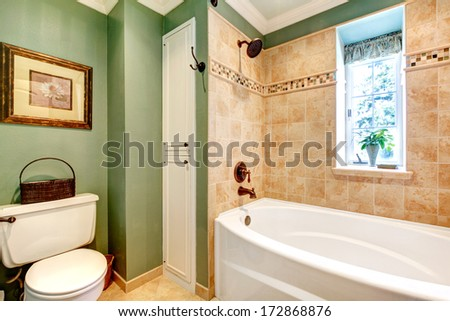 Olive and mocha tones bathroom with rustic picture and towel basket